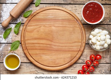 Cutting wooden board with pizza preparation ingridients: mozzarella, tomatoes sauce, basil, olive oil, cheese, spices. Italian pizza preparation wooden table. Traditional food.