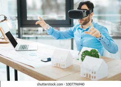 Cutting-edge technologies. Handsome young architect sitting at his work desk in the office and testing his new VR headset while taking a break from work on a blueprint