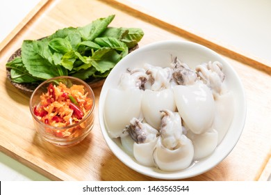 Cuttlefish or Cuttlefish Rainbow with holy basil leaves and pestle chili and garlic prepare for stir fried Cuttlefish with basil; top view on wooden background. Thailand's popular dishes (Pad Ga Pow).