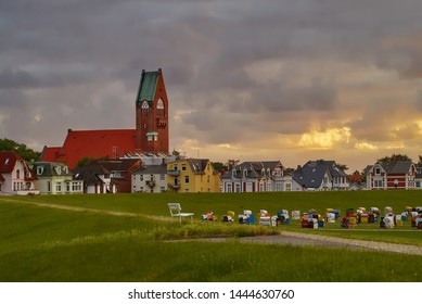 Cuxhaven, Germany - July 07, 2019: scenic sunset over the houses, dike and beach chairs at Grimmershörn bay next to the church St. Petri