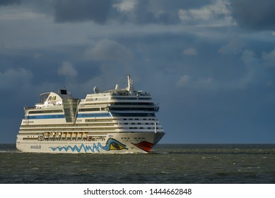 Cuxhaven, Germany - July 07, 2019: the cruise ship AIDA sol entering the Elbe river in the sunlight against a dark cloudy sky