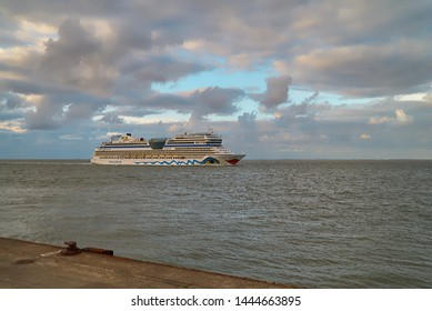 Cuxhaven, Germany - July 07, 2019: the cruise ship AIDA sol entering the Elbe river in front of a vivid cloudy sky