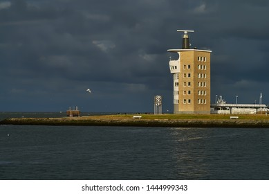 """Cuxhaven, Germany - July 07, 2019: Radar tower and viewing platform """"Alte Liebe"""" in front of a dramatic dark grey sky"""