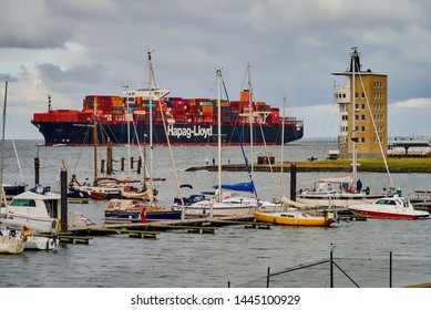 """Cuxhaven, Germany - July 07, 2019: large cargo ship """"Shanghai Express"""" by the company Hapag Lloyd loaded with containers passes the radar tower and viewing point """"Alte Liebe"""" against grey cloudy sky"""
