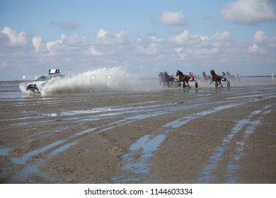 """Cuxhaven, Germany - July 22, 2018: start of the 8th race of """"Duhner Wattrennen"""", a harness racing on the mud flat under a vivid blue sky with clouds, water is splashing behind the start car"""