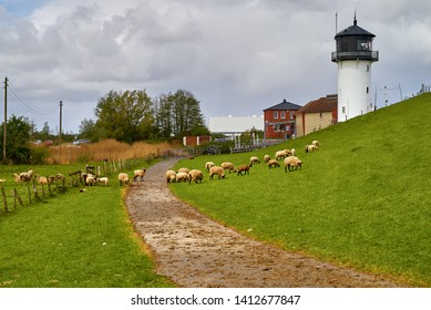 """Cuxhaven, Germany - May 03, 2019: the historic lighthouse """"Dicke Bertha"""" on the dike with sheep in front of vivid grey sky"""