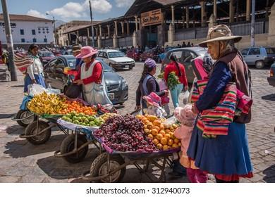 CUZCO, PERU - CIRCA 2015: Fruit sellers in the street circa 2015 in Cuzco, Peru.