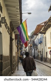 CUZCO, PERU - OCTOBER 13, 2016: The Cuzco flag flying on the left outside a building in Triunfo Street, which leads up to the Church of San Blas in the Historic Center of the city.