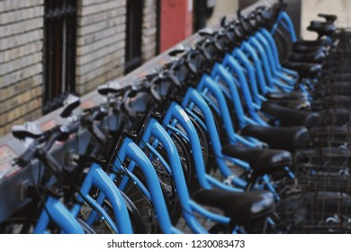 Cyan bicycles stand in a row. Parking, rent a bike. Cluj-Napoca, Romania.