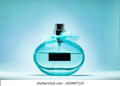 Cyan perfume glass bottle on light blue background. Eau de toilette. Eau de parfum. Beautiful composition of green blue perfume bottle.