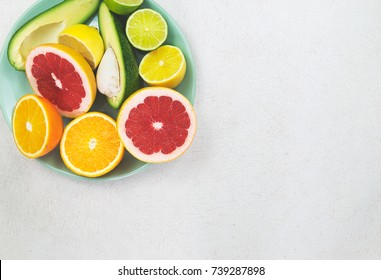 Cyan plate with sliced orange, grapefruit, lemon, lime and avocado on the old white table