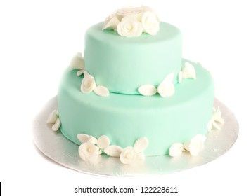 cyan and teal two tier tall cake with fondant flower decoration on white background