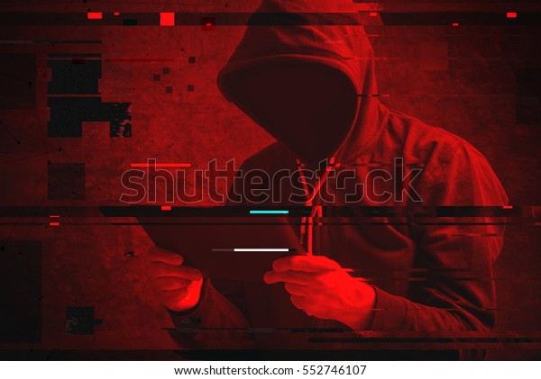 Cyber attack with unrecognizable hooded hacker using tablet computer, digital glitch effect