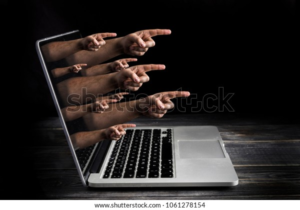Cyber bulling concept with fingers from the screen blame user