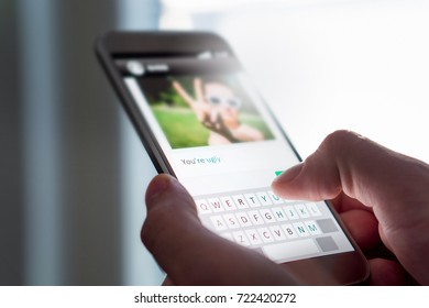 Cyber bullying, internet trolling and bad behavior online concept. Person writing mean comment to picture on an imaginary social media website with smart phone.