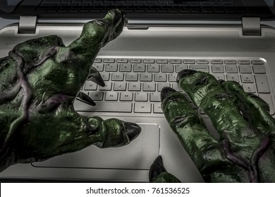 Cyber bullying, online fraud, computer virus or internet trolls concept with the hands of a troll typing on the keyboard of a laptop computer