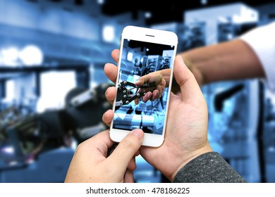 Cyber communication and robotic concepts. Industrial 4.0 Cyber Physical Systems concept. hand holding smart phone and robot and blur Engineerer human holding hand with handshake background
