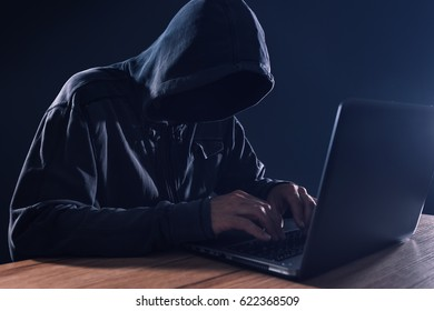 Cyber crime and computer virus concept with hooded faceless person working on laptop