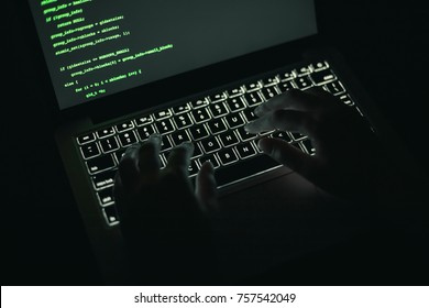 Cyber crime concept: hands of a person hacking on laptop in the darkness