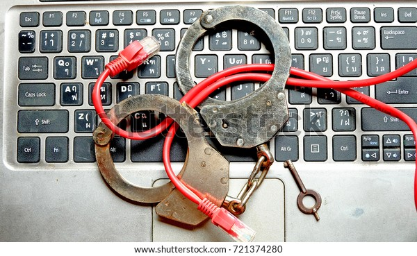 Cyber crime concept with   Police handcuff lock wire lan on notebook keyboard