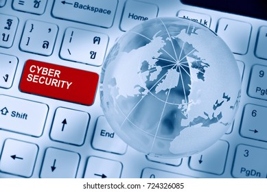 Cyber crime and cyber security concept : Words CYBER SECURITY inscribed or printed on a red enter button of a white desktop computer keyboard with a crystal clear sphere / globe and opaque world map.