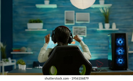Cyber gamer playing video game with new graphics winning championship, sitting in gaming room. Virtual space shooter game in cyberspace, esports player performing tournament on RGB profesional