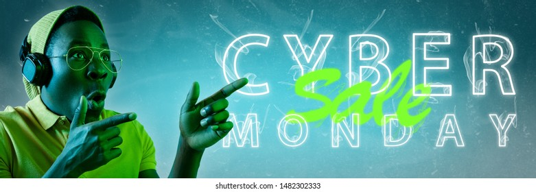 Cyber monday, sales, purchases concept. Neon lighted letters on gradient background. Astonished man pointing. Negative space. Modern design. Contemporary art. Creative conceptual and colorful collage.
