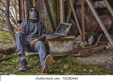 Cyber punk or fantastic or postapocalyptic or future world man cosplayer in goggles, skull mask and hood (maybe cyber junkie with wire from hand to laptop), inside of destructed radioactive  factory