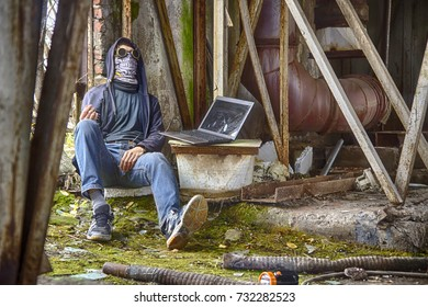 Cyber punk or fantastic or postapocalyptic or future world man cosplayer in goggles, skull mask and hood (maybe cyber junkie with wire from hand to laptop), inside of rusty mossy radioactive  factory