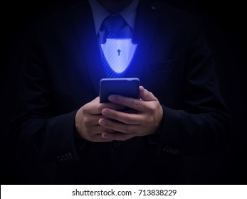 Cyber security concept, businessman in black suit hold mobile phone and shield graphic, protection from theft, hacker or damage to their hardware, software, data or information, against network risks