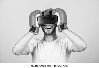 Cyber sport concept. Cyber coach online training. Cyber sportsman boxing gloves. Augmented 3D world. Man boxer virtual reality headset simulation. Man play game in VR glasses. Explore cyber space.