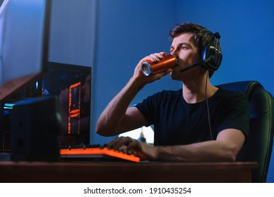 Cyber sport. Professional cybersport player training or playing online video game on his PC late at night, drinking caffeine energy drink to concentrate, focus on game. Team play. Games addiction