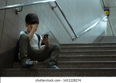 Cyberbullying concept. Young Asian preteen boy sitting at stair, covering his face with hands and other hand holding smartphone. Alone, stressed, frustrated, overwhelmed with online bullying.