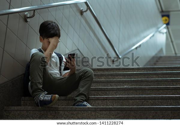 Concepto de ciberacoso. Joven adolescente/adolescente asiático sentado en el escalón, cubriendo su cara con la mano, sosteniendo el smartphone. Solo, estresado, frustrado, abrumado, llorando, deprimido, tecnológico.