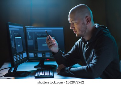 cybercrime, hacking and technology concept - male hacker with smartphone and progress loading bar on computer's screens in dark room