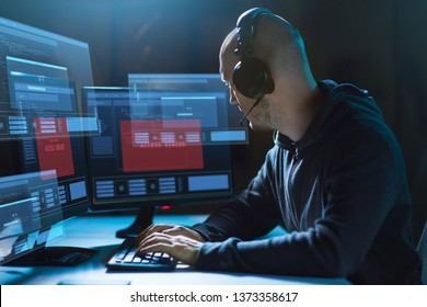cybercrime, hacking and technology concept - male hacker in headset with access denied messages on computer's screens wiretapping or using computer virus program for cyber attack in dark room