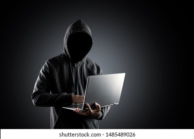 Cybercrime, hacking and technology crime. no face hacker with laptop on black background with clipping path.