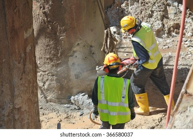 CYBERJAYA, MALAYSIA � NOVEMBER 21, 2015: Construction workers using mobile concrete hacker to hack concrete pile at the construction site in Cyberjaya, Malaysia