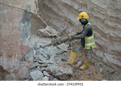 CYBERJAYA, MALAYSIA â?? SEPTEMBER 15, 2015: A construction workers using mobile concrete hacker to hack concrete pile at the construction site.