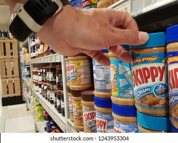 Cyberjaya, Selangor. October 26, 2018. Customer pickup a Skippy peanut butter bottle from display shelf at Jaya Grocer Supermarket at Cyberjaya, Selangor