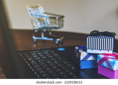 Cybermonday and Blackfriday Shopping online. Some gifts on a laptop keyboard with a trolley on the background. E-commerce sale concept.