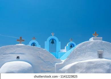 Cycladic greek orthodox church on Paros island, Greece. White crosses against blue sea and sky