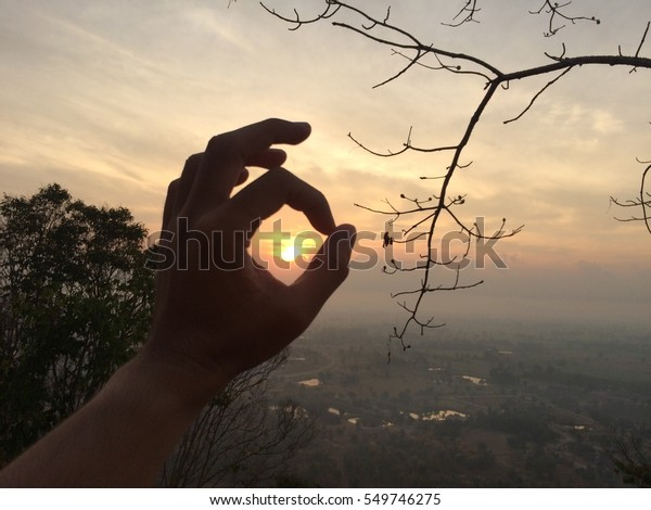 Cycle Hand in Sunrise on sky from mountain and trees, Thailand