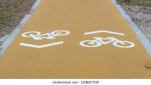 Cycle path with two lanes, and directions marked on the ground. Yellow asphalt and white bicycles painted.