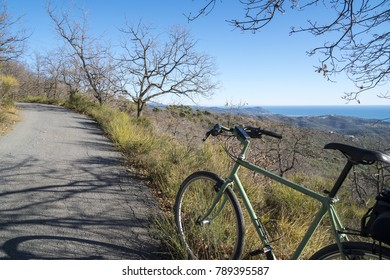 Cycle tourism in Italy: a green bicycle on a country road with a seascape in the background.