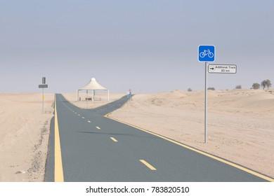 Cycle track through the arid sand desert landscape near Dubai in the UAE, Arabia, Middle East