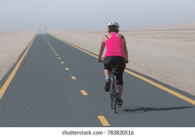 Cycle track through the arid sand desert landscape near Dubai in the UAE, Arabia, Middle East
