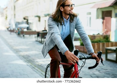 Cycle To Work. Stylish Male Cycling On Bicycle On Street. Portrait Of Handsome Young Smiling Man In Fashionable Men's Clothes Riding On Bike Outdoors. High Quality Image.