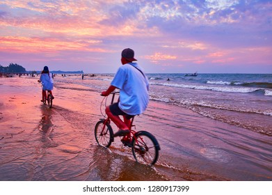The cyclers enjoy the beach on Bay of Bengal, riding along the swash line on sunset, Chaung Tha, Myanmar.