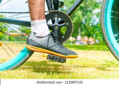 Cycler`s foot on pedal bicycle in a park at summer